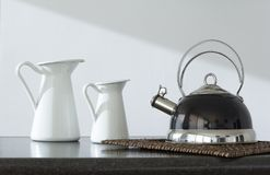 Coffee pot and two teapots on the table royalty free stock photos