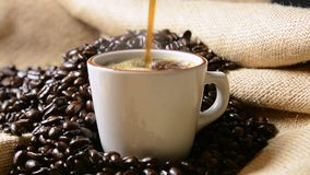 Coffee pour. A cup of coffee being poured in a background of coffee beans stock video