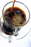 Coffee Poured. Black coffee pouring into glass cup stock photo