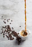 Coffee poured into a cup and coffee beans around Stock Photo