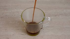 Coffee is poured into a cup. Pour coffee in a transparent cup, standing on a bright table stock video footage