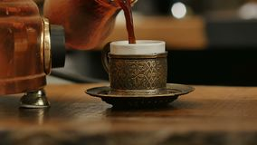 Coffee poured in a cup from the Turks. Close up. Slow motion. Professional shot in HD resolution. 089. You can use it e.g. in your commercial video, business stock footage