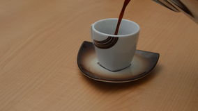 Coffee Poured into Small Cup. Footage of strong black coffee being poured into a small cup on a wooden background stock footage