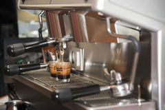 Coffee pouring into shot glasses. Royalty Free Stock Photos