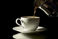 Coffee pouring into white cup isolated Stock Image
