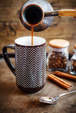 Coffee pours from a copper cezve into a brown mug Stock Photography