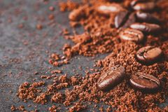 Coffee powder and beans. Close-up of coffee powder and beans splash on black wooden board royalty free stock image