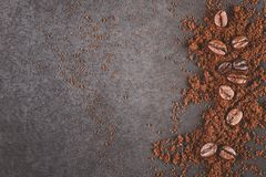 Coffee powder and beans. Splash on black wooden board, top view stock photos