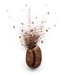 Coffee powder burst from coffee bean. Isolated on white background Royalty Free Stock Photo