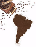 Coffee powder in the shape of South America and a coffee mill.(series) Royalty Free Stock Image
