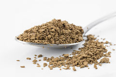 Coffee powder on spoon. Close focus on premium brown decaf coffee powder putting on stainless steel teaspoon and white floor which isolated on white background royalty free stock images