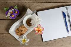 Coffee powder and sugar in cup with cookies,open notebook Royalty Free Stock Image