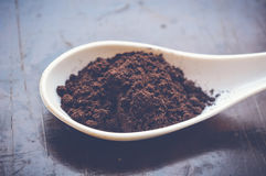 Coffee powder. On white spoon on wooden table stock image