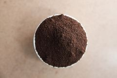 Coffee powder in a cup. On wooden background in close up royalty free stock image