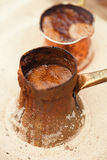 Coffee preparation in copper pot with hot golden sand outdoor Royalty Free Stock Photos