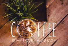 Coffee quote for coffee lover. Top view of a milk ice coffee in a mug on the wooden table with quotes Coffee is My Love Language stock images