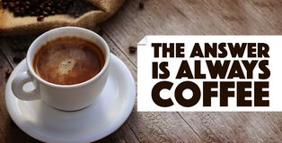 Coffee Quote. Over A Cup of hot coffee on wooden surface royalty free stock image
