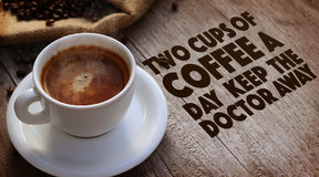 Coffee Quote. Over cup of coffee on wooden surface stock photos