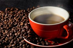 Coffee in red cup and coffee beans are the background. Stock Photo