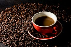 Coffee in red cup and coffee beans are the background. Hot coffee in red cup and coffee beans are the background Royalty Free Stock Photo