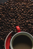 Coffee in red cup and coffee beans are the background. Royalty Free Stock Photography