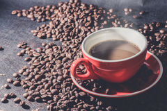 Coffee in red cup and coffee beans are the background. Royalty Free Stock Images