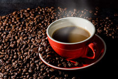 Coffee in red cup and coffee beans are the background. Stock Image