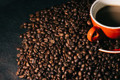 Coffee in red cup and coffee beans are the background. Royalty Free Stock Photo