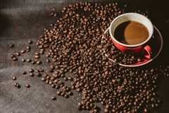 Coffee in red cup and coffee beans are the background. Hot coffee in red cup and coffee beans are the background Stock Photo
