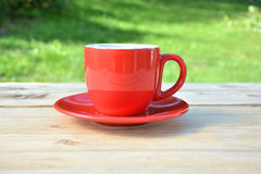 Coffee in red cup in garden Royalty Free Stock Photo