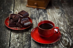 Coffee red cup, pieces of chocolate on wooden table background. Tinted. Selective focus. Coffee red cup, pieces of chocolate on the wooden table background Royalty Free Stock Images