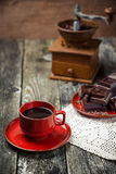 Coffee red cup, pieces of chocolate on wooden table background. Tinted. Selective focus. Coffee red cup, pieces of chocolate on the wooden table background Royalty Free Stock Photos