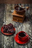 Coffee red cup, pieces of chocolate on wooden table background. Tinted. Selective focus. Coffee red cup, pieces of chocolate on the wooden table background Royalty Free Stock Image