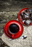 Coffee red cup, pieces of chocolate on wooden table background. Tinted. Top view. Coffee red cup, pieces of chocolate on the wooden table background. Tinted Royalty Free Stock Photos