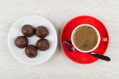 Coffee in red cup on saucer, spoon and chocolate candy. In plate on wooden table. Top view Royalty Free Stock Image