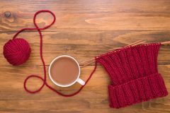 Coffee and red knitting on wooden background Royalty Free Stock Images