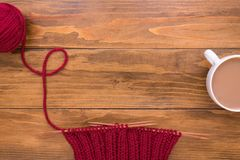 Coffee and red knitting on wooden background Stock Photography