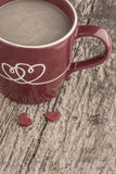 Coffee in a red mug with hearts on wooden table Stock Photography