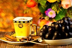 Coffee refreshing drink, and the grapes are a delicious delicacy on the background of summer garden flowers and holiday lights. Bokeh.  Grapes healthy food royalty free stock photography