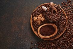 Coffee roasted beans in cup and scattered nearby, ground coffee and cane sugar on a brown table background. Top view with space to