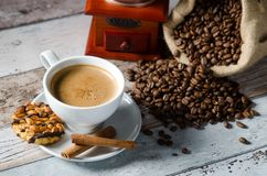 Coffee, roasted beans, mill grinder and some sweets Stock Photos