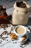 Coffee, roasted beans, mill grinder and some sweets. Coffee, roasted beans, mill grinder and cookie with nuts on wooden background Royalty Free Stock Image