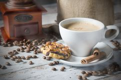 Coffee, roasted beans, mill grinder and some sweets Royalty Free Stock Photos