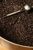 Coffee roaster bean cooling. The freshly roasted beans from a large coffee roaster, just before the beans are stirred in the cooling cylinder. Beans are shiny stock image