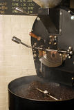 Coffee roaster cooling. The freshly roasted beans from a large coffee roaster, just as the beans are stirred in the cooling cylinder. Smoke rises while the dark stock photo
