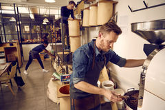 Coffee roastery and distribution company with men at work. Men working in a modern coffee bean roastery with bags of raw beans and simple storage containers royalty free stock photography