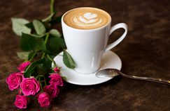A fresh morning cappuccino in a white cup with a heart of foam, stands on a wooden table, near it lies a rose. Coffee with a rose, beautifully decorated Stock Photo