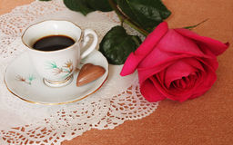 Coffee with a rose. Still Life with cup of coffee and a pink rose on a lace salfete Stock Images
