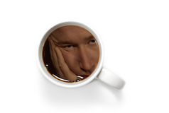 Coffee's reflection. A mans sleepy reflection in a cup of coffee before he drinks it Royalty Free Stock Photography