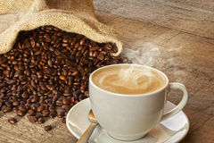 Coffee and Sack of Coffee Beans. A cup of hot steaming espresso coffee on a rustic plank background, with a sack of coffee beans. Front to back focus Stock Photo